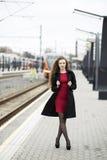 Kvinna på den röda klänningen och svartöverrocken Fotografering för Bildbyråer