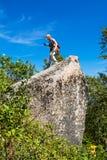 Kvinna på den stora stenen under att fotvandra Fotografering för Bildbyråer