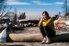 Kvinna på det brända förstörda huset och gården, efter brandkatastrof royaltyfri fotografi