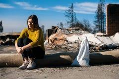 Kvinna på det brända förstörda huset och gården, efter brandkatastrof fotografering för bildbyråer