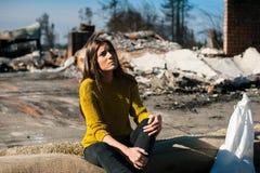Kvinna på det brända förstörda huset och gården, efter brandkatastrof royaltyfria foton