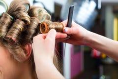 Kvinna på det krullande håret för frisör arkivfoto