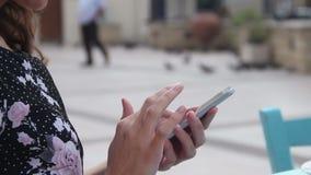 Kvinna på det utomhus- kafét genom att använda mobilen app på smartphonen, smsa som överför mejl lager videofilmer