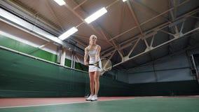 Kvinna på domstolen som upp kastar bollen, medan spela tennis arkivfilmer