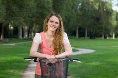 Kvinna på en cykel i en parkera Arkivbilder