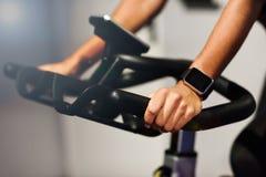 Kvinna på en idrottshall som inomhus gör snurr eller cyclo med den smarta klockan royaltyfria bilder
