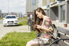 Kvinna på en stadsbänk med en smartphone Arkivfoton