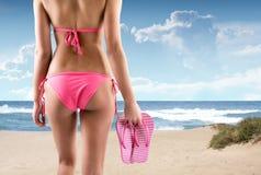 Kvinna på en strand med bikinin och flipmisslyckanden Arkivfoto