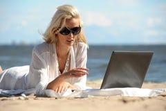Kvinna på en strand med en bärbar dator Arkivbild