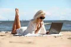 Kvinna på en strand med en bärbar dator Fotografering för Bildbyråer