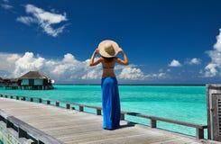 Kvinna på en strandbrygga på Maldiverna Royaltyfria Bilder