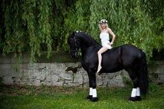 Kvinna på en svart häst Arkivfoto
