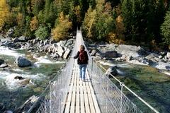 Kvinna på en upphängningbro Arkivbild
