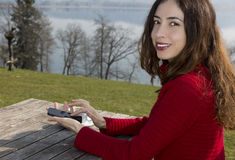 Kvinna på en utomhus- restaurang som bläddrar med hennes smarta telefon Royaltyfria Bilder