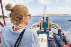 Kvinna på färjatur till deras destination för ö för sommarsemestrar arkivfoto