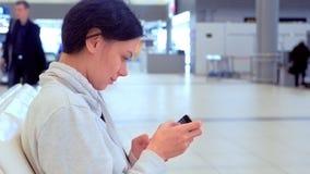 Kvinna på flygplatsen med en mobiltelefon, i hennes meddelande och att vänta på för händer smsande hennes flyg, sidosikt stock video