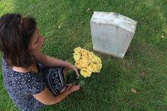 Kvinna på graven för ` s för okänd soldat med gula blommor fotografering för bildbyråer