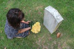 Kvinna på graven för ` s för okänd soldat med gula blommor arkivfoton