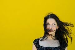 Kvinna på gul bacjground Fotografering för Bildbyråer