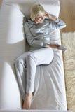 Kvinna på hållande ögonen på TV för soffa Royaltyfria Foton