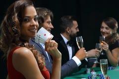 Kvinna på hållande champagne för rouletttabell som är glass i kasino arkivfoto
