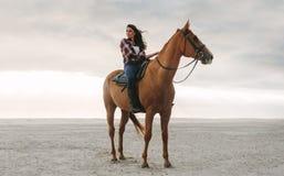 Kvinna på hennes häst på stranden royaltyfri bild