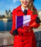 Kvinna på invallning nära Notre Dame de Paris visningflagga Arkivbild