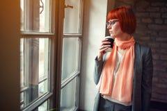 Kvinna på jobb som dricker kaffe vid fönstret royaltyfria foton