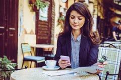 Kvinna på kafét, genom att använda telefonen för att kontrollera kreditkorten arkivbild