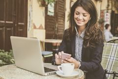 Kvinna på kafét som arbetar på bärbara datorn, genom att använda telefonen arkivfoton
