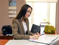 Kvinna på kontorsskrivbordet som undertecknar ett avtal Royaltyfria Bilder