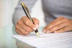 Kvinna på kontorsskrivbordet som undertecknar ett avtal med den grunda fokusen på si Arkivfoto