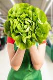 Kvinna på livsmedelsbutiken som döljer bak grönsallat royaltyfria foton