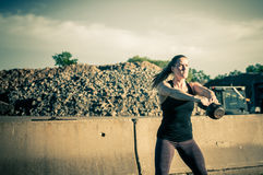 Kvinna på mitt av kettlebellgunga Fotografering för Bildbyråer
