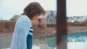 Kvinna på pir vid floden lager videofilmer