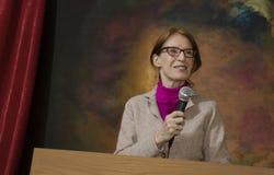 Kvinna på podiet med microphone_1 arkivbild