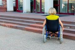 Kvinna på rullstolen och trappa royaltyfri bild