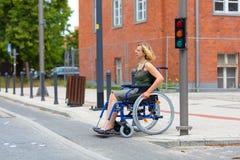 Kvinna på rullstolen som korsar gatan Royaltyfri Foto