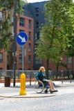 Kvinna på rullstolen som korsar gatan Royaltyfri Bild