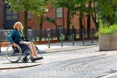 Kvinna på rullstolen som korsar gatan Arkivfoto