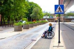 Kvinna på rullstolen som korsar gatan Arkivbild