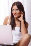 Kvinna på säng genom att använda bärbara datorn Royaltyfri Fotografi