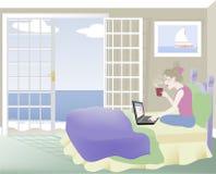 Kvinna på säng med bärbar dator Arkivfoto
