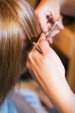 Kvinna på skönhetsalongen som rätar ut hår Royaltyfria Bilder