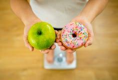Kvinna på skala som mäter viktinnehaväpplet och donuts som väljer mellan sund eller sjuklig mat royaltyfri bild