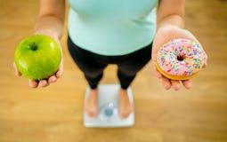 Kvinna på skala som mäter viktinnehaväpplet och donuts som väljer mellan sund eller sjuklig mat fotografering för bildbyråer
