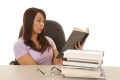 Kvinna på skrivbordet med en bunt av bokohh Royaltyfria Bilder