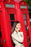 Kvinna på smartphonen vid London det röda telefonbåset Arkivbilder