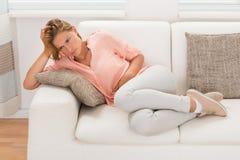 Kvinna på Sofa Having Stomachache Royaltyfri Bild
