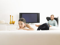 Kvinna på Sofa And Man In Armchair i modern vardagsrum Arkivbild